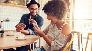 Dos personas mirando un teléfono y riendo en una cafetería.