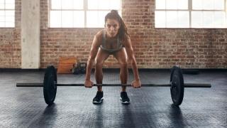 Mujer en el gimnasio levantando mucha carga.