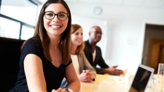 Mujer sonriente con sus colegas de trabajo.