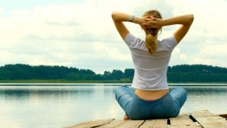 Mujer meditando junto al lago.