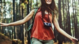 Mujer con una cámara en el bosque.