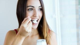 Mujer comiendo una gran cucharada de yogur.