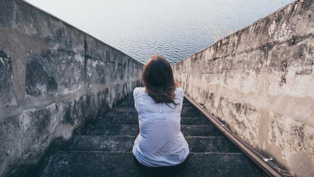 Mujer sentada en escalones junto al mar.
