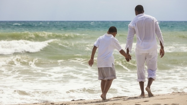 Padre e hijo caminando por la playa.