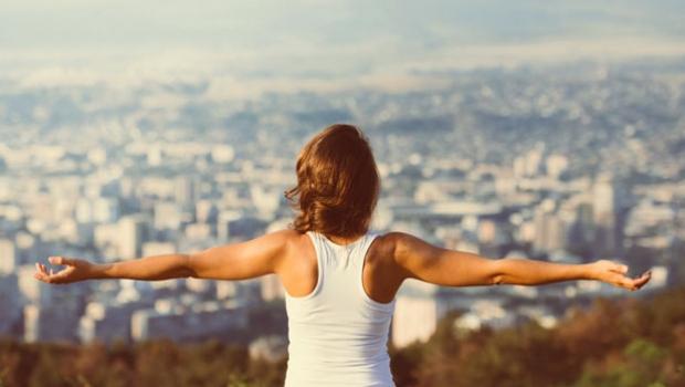 Mujer abriendo los brazos en lo alto de una colina.