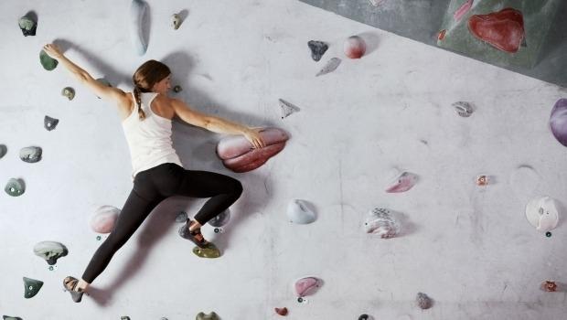 Mujer trepando un muro de escalada