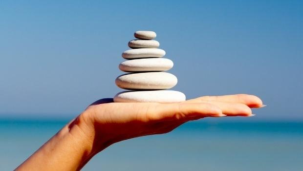 Piedras equilibradas sobre una mano frente al océano