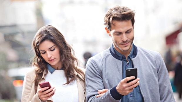 Dos personas mirando sus teléfonos.