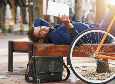Persona leyendo su tablet al aire libre.