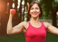 Mujer feliz de cuarenta y tantos levantando pesas en el parque.