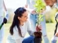Mujer haciendo tareas voluntarias en un jardín con un grupo de gente.