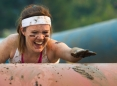 Mujer participando en una pista llena de lodo.